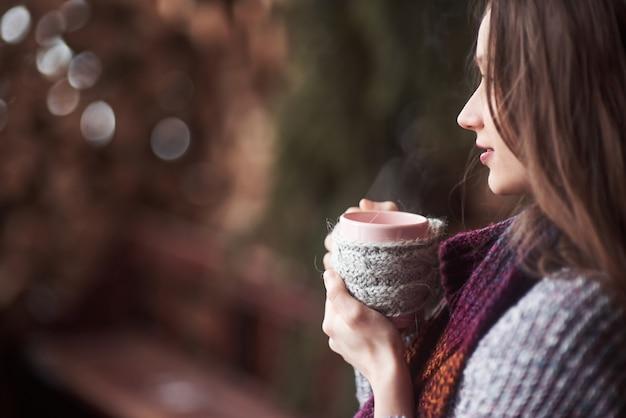 Oman indossando abiti in maglia calda che beve tazza di tè caldo o caffè all'aperto Foto Premium
