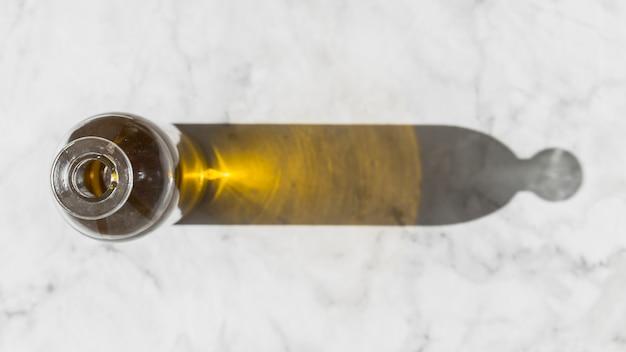 Ombra della bottiglia di olio su fondo di marmo bianco Foto Gratuite