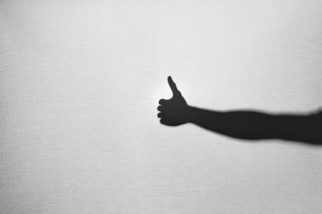 Ombra della mano che mostra pollice in su Foto Gratuite