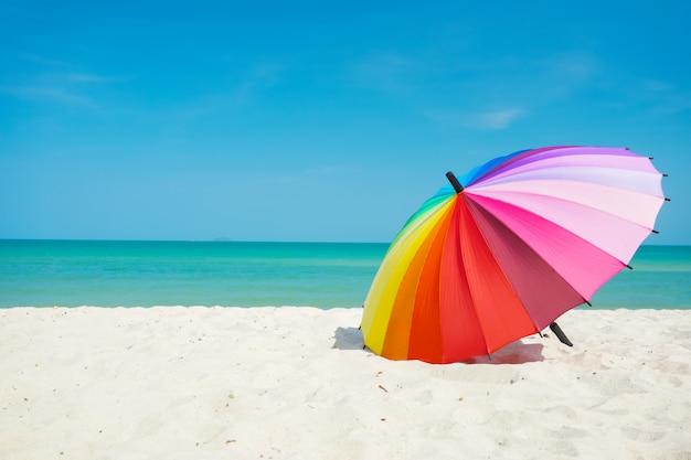Ombrello arcobaleno sulla spiaggia di sabbia Foto Premium