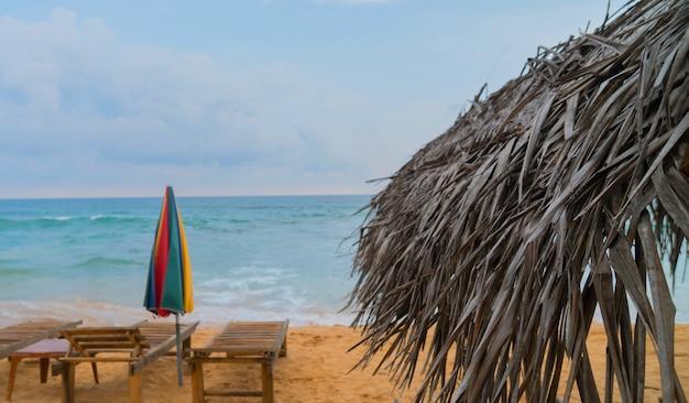 Ombrello di canna sulla spiaggia nell'oceano Foto Premium