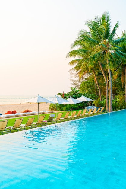 Ombrello e sedia intorno alla piscina con la vista sull'oceano del mare per il concetto di viaggio di vacanza di festa Foto Premium