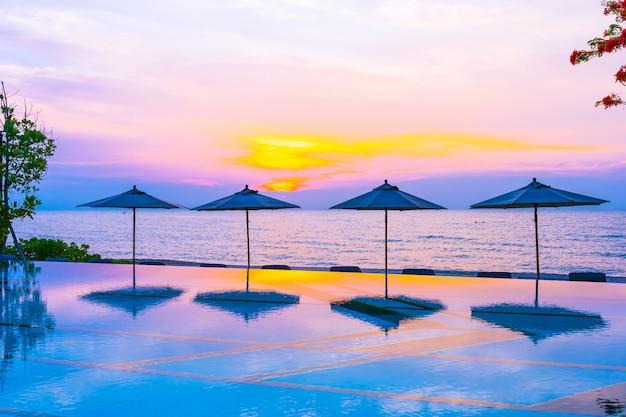 Ombrello e sedia intorno alla spiaggia vicino all'oceano del mare della piscina ad alba o tempo di tramonto Foto Gratuite