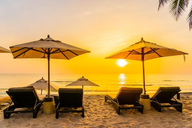 Ombrello e sedia sulla bellissima spiaggia e mare al sorgere del sole per viaggi e vacanze Foto Gratuite