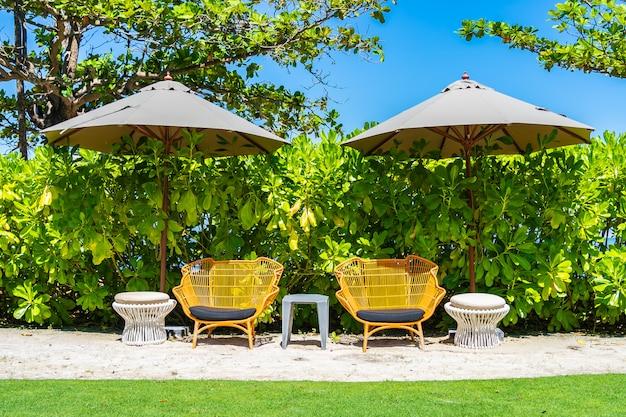 Ombrello e sedia sulla spiaggia e sul mare con cielo blu Foto Gratuite