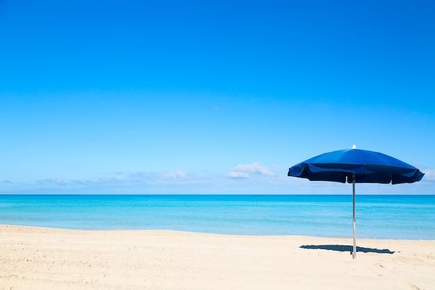 Ombrellone blu sulla spiaggia tropicale Foto Premium