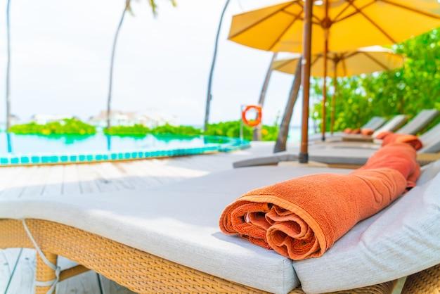 Ombrellone e sedia intorno alla piscina dell'hotel resort Foto Premium