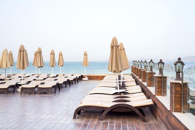 Ombrelloni color beige e lettini con vista sul mare. concetto di vacanza. Foto Premium