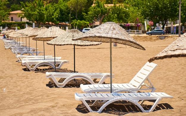 Ombrelloni di paglia con sedie a sdraio su una spiaggia