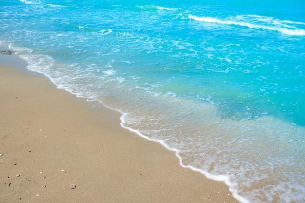 Onda di acqua blu sulla sabbia della spiaggia Foto Premium