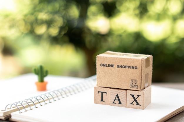 Online shopping box pagare reddito annuale (tax) per l'anno sul calcolatore. Foto Premium