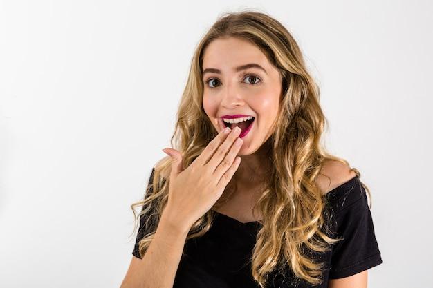 Oops! chiuda sul ritratto della ragazza bionda sexy, bella, impressa, stupita che tiene la sua mano vicino alla bocca Foto Premium