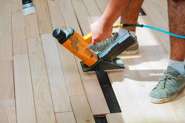 Operaio del carpentiere che installa la scheda di legno del parquet Foto Premium