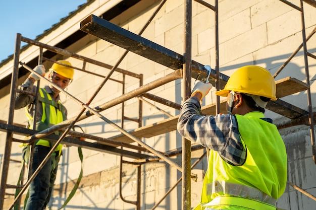 Operaio edile che indossa cintura di sicurezza durante il lavoro in alto, concetto di edificio residenziale in costruzione. Foto Premium