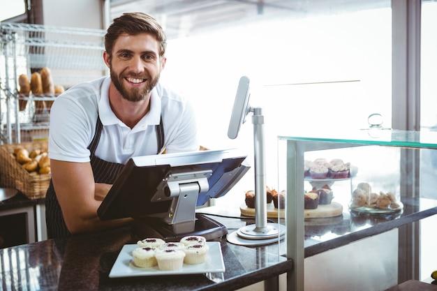 Operaio sorridente in posa dietro il bancone Foto Premium