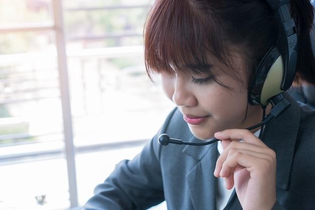 Operatore amichevole della giovane donna o agente di call center asiatico con le cuffie avricolari che funzionano nel call center Foto Premium