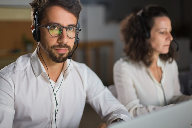 Operatore di call center bello in occhiali che guarda l'obbiettivo Foto Gratuite