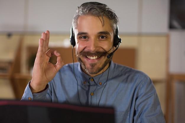 Operatore di call center felice che esamina macchina fotografica e che mostra segno giusto Foto Gratuite