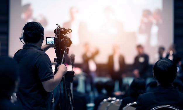 Operatore di videocamera che lavora con la sua attrezzatura all'evento al coperto Foto Premium
