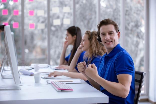 Operatore uomo seduto pollice in alto a una scrivania davanti al computer. Foto Premium