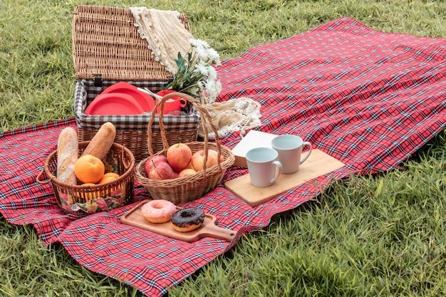 Ora legale primo piano del cestino da picnic con cibo e frutta in natura. Foto Premium