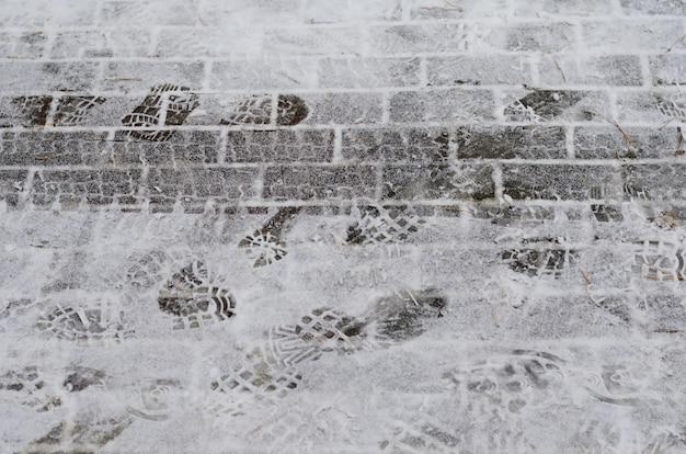 Orario invernale - strada coperta di neve con tracce di pneumatici per auto e impronte di scarpe Foto Premium