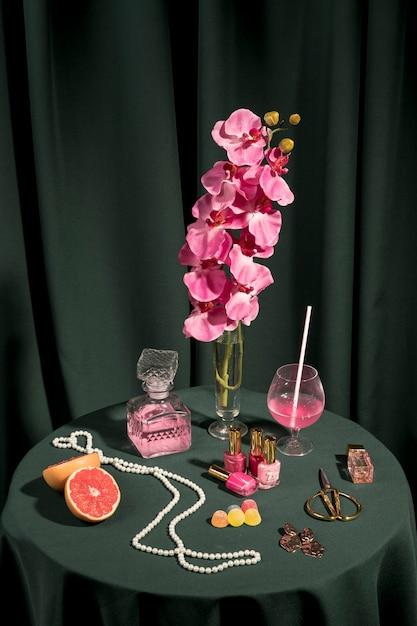 Orchidea rosa ad alto angolo accanto a oggetti di moda Foto Gratuite