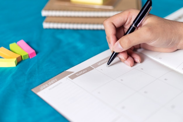 Ordine del giorno e programma di pianificazione della donna usando il pianificatore di eventi del calendario Foto Premium