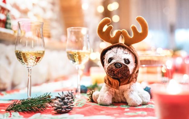 Orecchie da portare della renna del giocattolo farcito del cane che si siedono sulla tabella vicino ai vetri del champagne sulla priorità bassa di feste di natale Foto Premium