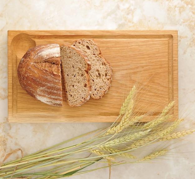 Orecchie del grano e del pane sul bordo di legno Foto Premium