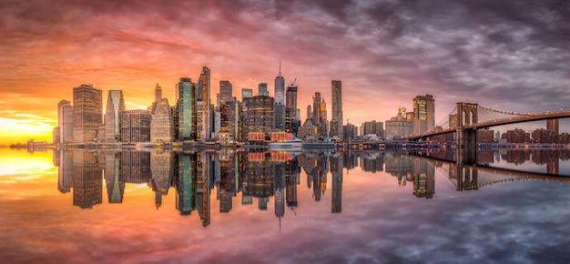 Orizzonte di new york city con i grattacieli al tramonto Foto Premium