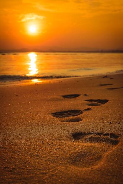 Orme sulla spiaggia al tramonto Foto Premium