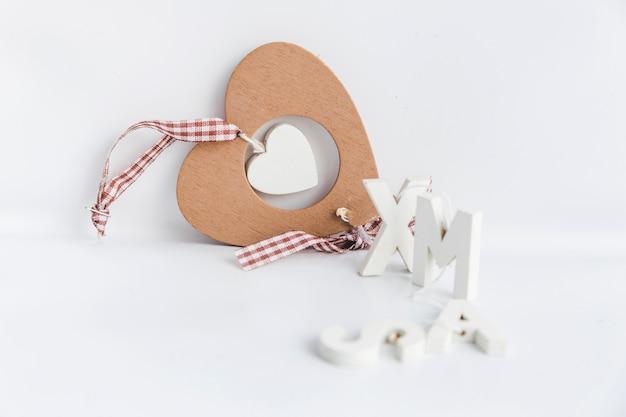 Ornamento di legno di forma del cuore con il testo di natale isolato sopra fondo bianco Foto Gratuite
