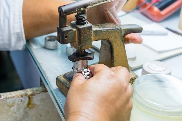 Orologiaio anziano che ripara un vecchio orologio da tasca Foto Premium