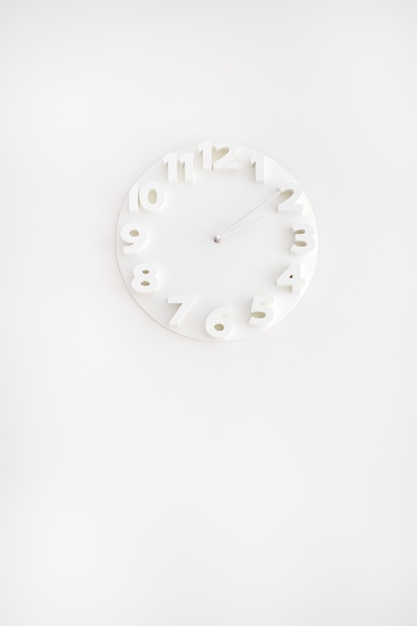 Orologio bianco sul muro bianco Foto Premium