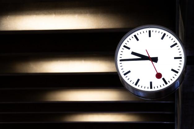 Orologio classico appeso al muro di cemento. Foto Premium