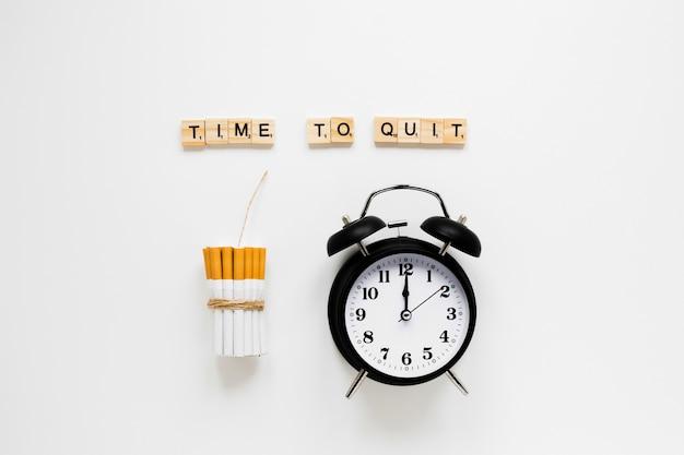Orologio con vista dall'alto con sigarette e parole Foto Gratuite