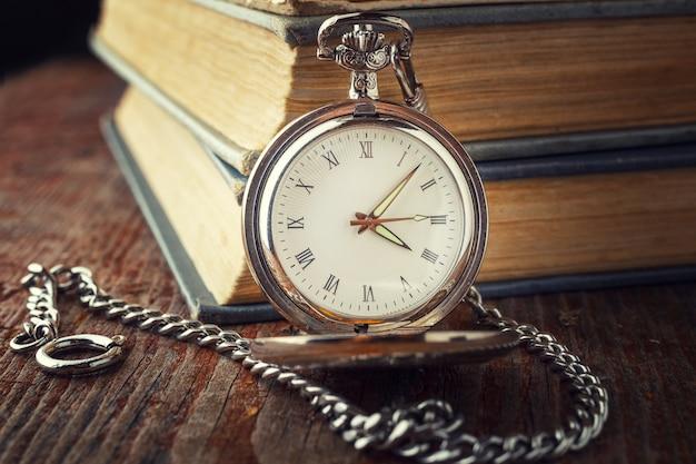 Orologio d'epoca su una catena su uno sfondo di vecchi libri Foto Premium