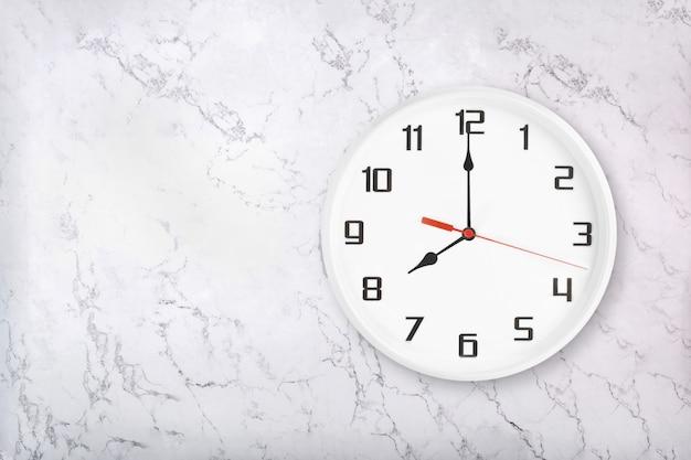 Orologio da parete rotondo bianco su sfondo di marmo naturale bianco. otto in punto Foto Premium