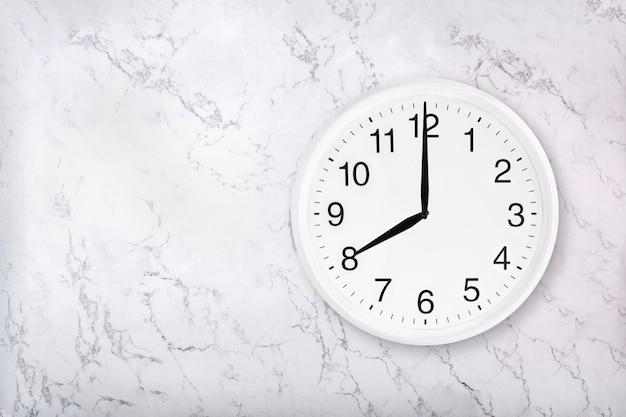 Orologio da parete rotondo bianco su sfondo di marmo. otto in punto. Foto Premium