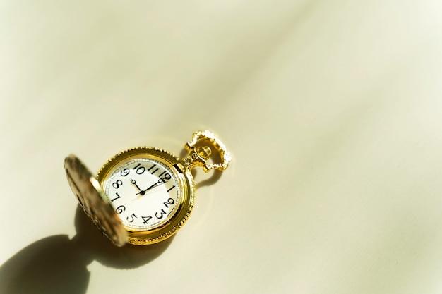 Orologio da tasca dorato sul tavolo con luce solare Foto Premium