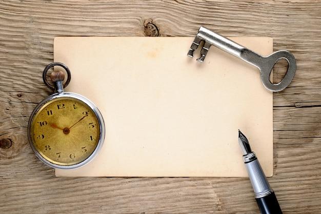 Orologio da tasca vintage, penna stilografica, chiave e vecchia cartolina Foto Premium