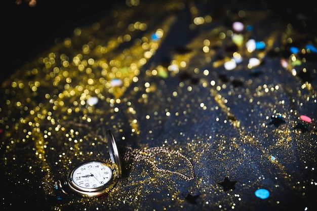Orologio da taschino con paillettes sul tavolo Foto Gratuite
