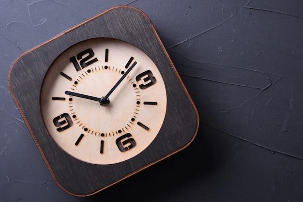 Orologio in legno fatto a mano sul tavolo di legno. avvicinamento. Foto Premium