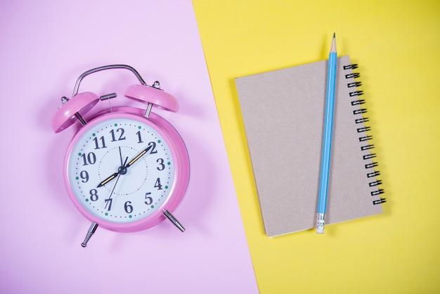 Orologio rosa sullo sfondo colorato, concetto di educazione Foto Gratuite