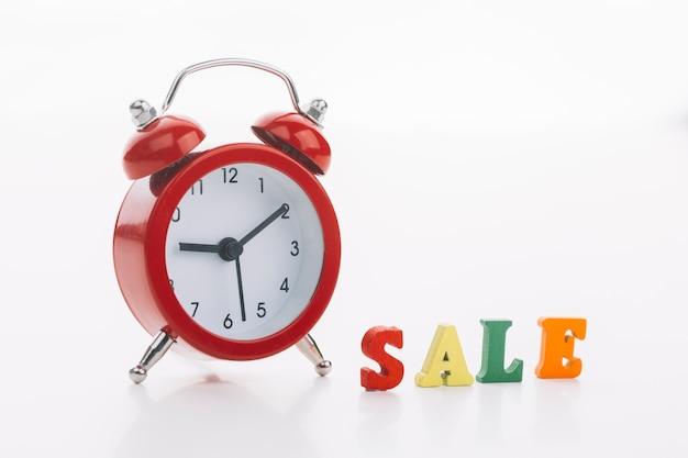 Orologio rosso con il concetto di vendita Foto Gratuite