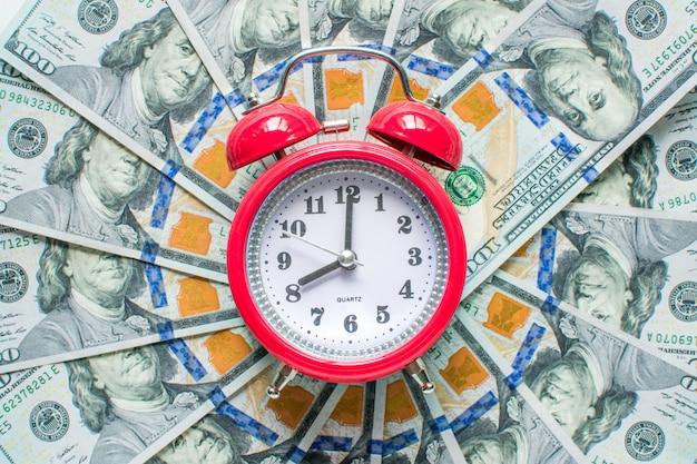 Orologio rosso sullo sfondo di dollari di denaro Foto Premium