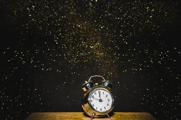 Orologio sul tavolo con paillettes che cadono Foto Gratuite