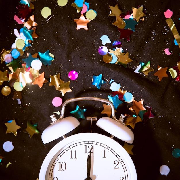 Orologio vista dall'alto circondato da coriandoli colorati Foto Gratuite