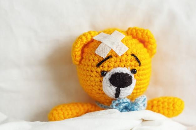 Orsacchiotto giallo malato con gesso sulla testa in camera da letto bianca. Foto Premium